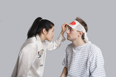 Young female doctor examining an injured male patient Royalty Free Stock Image