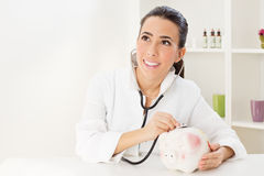 Young female doctor examining a Piggy Bank Royalty Free Stock Images