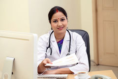 Young female doctor giving patient documents Royalty Free Stock Photos