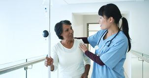 Young female doctor greeting patient in hospital corridor 4k. Waist up view of young Asian female doctor warmly greeting a senior mixed race female patient in a stock video footage