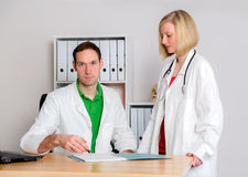 Young female doctor in her office. Two young  family doctor in her office woking together Royalty Free Stock Photos