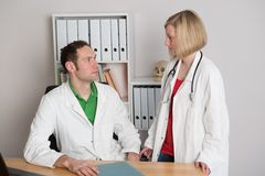 Young female doctor in her office. Two young  family doctor in her office woking together Royalty Free Stock Image