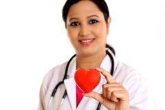 Young female doctor holding a beautiful red heart shape. Happy young female doctor holding a beautiful red heart shape Royalty Free Stock Photos