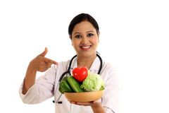 Young female doctor holding bowl of vegetables Stock Photo