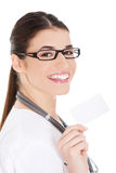 Young female doctor holding business card. Royalty Free Stock Photos