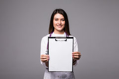 Young female doctor holding empty folder with files of desease illness. Specialist point by pen blank clipboard. Woman in medical. Results and information of Royalty Free Stock Photo