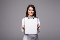 Young female doctor holding empty folder with files of desease illness. Specialist point by pen blank clipboard. Woman in medical. Results and information of Royalty Free Stock Images