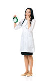 Young female doctor holding a green alarm clock Stock Photography