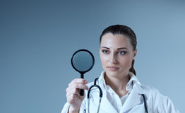 Young female doctor holding magnifying glass in ri Stock Photo