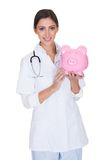 Young Female Doctor Holding Piggy Bank. Isolated On White Stock Photography