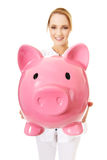 Young female doctor holding a piggybank. Royalty Free Stock Images