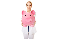 Young female doctor holding a piggybank. Stock Photo