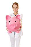 Young female doctor holding a piggybank. Royalty Free Stock Photos