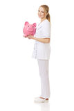 Young female doctor holding a piggybank. Royalty Free Stock Photo