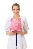 Young female doctor holding a piggybank. Stock Image