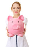 Young female doctor holding a piggybank. Royalty Free Stock Image
