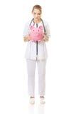 Young female doctor holding a piggybank. Stock Photos