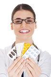 Young female doctor holding pills. Stock Photo