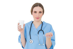 Young female doctor holding a plastic cup and presenting with her hand Royalty Free Stock Image