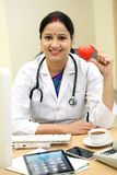Young female doctor holding red heart shape. Young woman doctor holding red heart shape royalty free stock images
