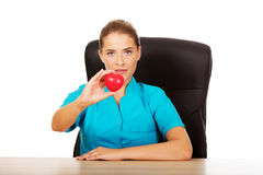 Young female doctor holding toy heart.  royalty free stock photography