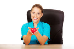Young female doctor holding toy heart.  stock photos