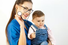 A young female doctor holds a baby in her arms and the baby is smiling at a stethoscope. White background royalty free stock image
