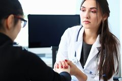 Young female doctor holds sick patient by hand. Expressing condolences and sympathy reports bad news about loss of loved ones due to cancer deadly aids disease royalty free stock photos