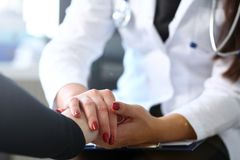 Young female doctor holds sick patient by hand. Expressing condolences and sympathy reports bad news about loss of loved ones due to cancer deadly aids disease royalty free stock image