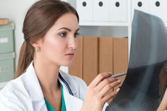 Young female doctor looking at lungs x-ray image Stock Photo