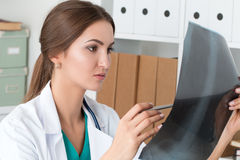 Young female doctor looking at lungs x-ray image Royalty Free Stock Image
