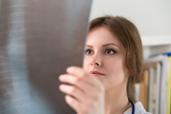 Young female doctor looking at lungs x-ray Stock Photos