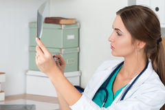 Young female doctor looking at lungs x-ray image Stock Photos