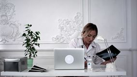 Young female doctor looking for x-ray photo and making notes. stock image