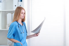 Young female doctor looking at the x-ray picture Royalty Free Stock Photos