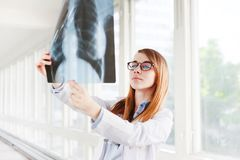 Young female doctor looking at the x-ray picture of lungs in hospital stock photography