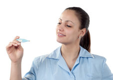 Young female doctor looking at thermometer Royalty Free Stock Photo