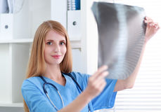 Young female doctor looking at the x-ray picture Royalty Free Stock Images