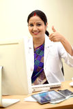 Young female doctor making thumbs up gesture Stock Images