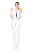 Young female doctor, nurse holding an apple and doughtnuts. Royalty Free Stock Photos