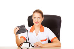 Young female doctor or nurse holding blood pressure gauge Royalty Free Stock Photography