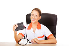 Young female doctor or nurse holding blood pressure gauge Royalty Free Stock Image