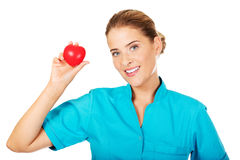 Young female doctor or nurse holding heart toy.  royalty free stock photography