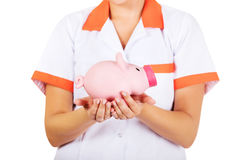 Young female doctor or nurse holding a piggybank Royalty Free Stock Photo