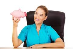 Young female doctor or nurse holding piggybank Royalty Free Stock Photos