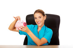 Young female doctor or nurse holding piggybank Royalty Free Stock Photo