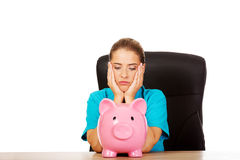 Young female doctor or nurse holding piggybank Royalty Free Stock Photography