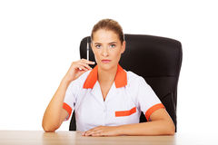 Young female doctor or nurse sitting behind the desk and holding syringe Royalty Free Stock Image