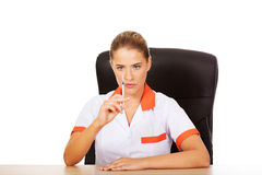Young female doctor or nurse sitting behind the desk and holding syringe Royalty Free Stock Images