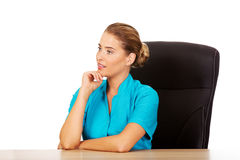 Young female doctor or nurse sitting behind the desk and talking with someone Royalty Free Stock Photos